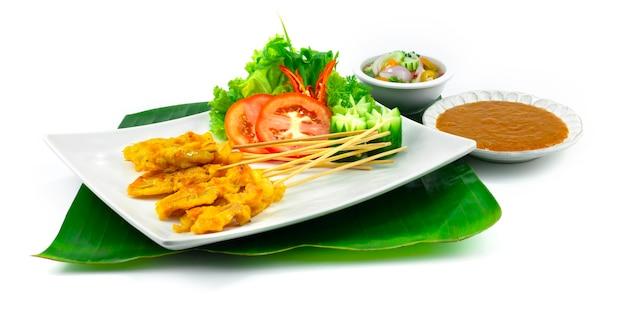 Varkenssaté of gegrild varkensvlees in spiesjes geserveerd met dipsaus, chili pindasaus, zoetzure saus thais eten decoratie met snijgroenten zijaanzicht