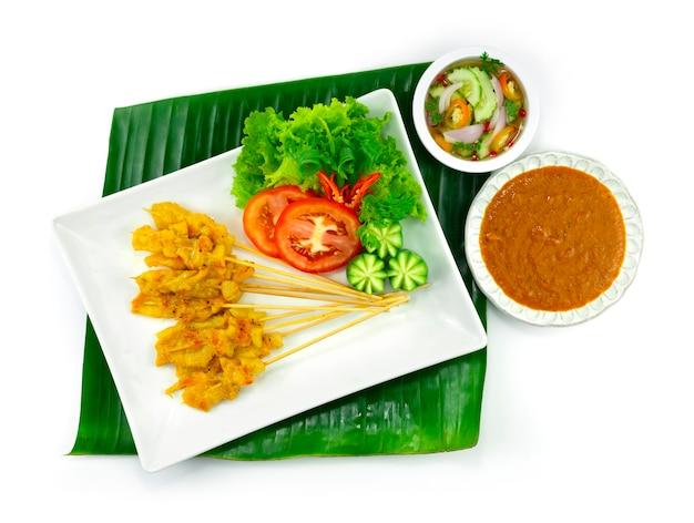 Varkenssaté of gegrild varkensvlees in spiesjes geserveerd onderdompeling chili pindasaus, zoetzure saus thais eten decoratie met snijwerk groenten bovenaanzicht