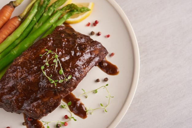 Varkensvlees geroosterde, gegrilde spareribs van een zomerse bbq geserveerd met groenten, asperges, worteltjes, verse tomaten en kruiden. gerookte ribben in witte plaat op stenen oppervlak. bovenaanzicht.