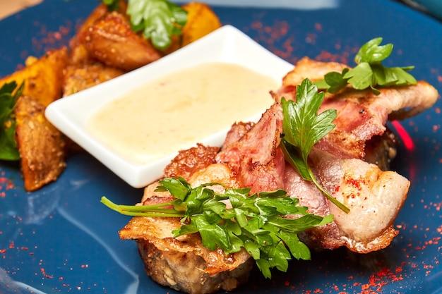 Varkensvlees in spek met gebakken aardappelen op een blauw bord
