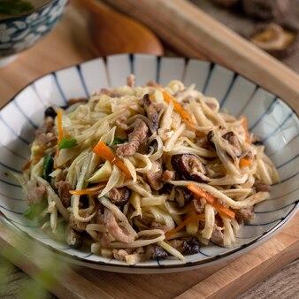 Varkensvlees julienne gebakken met water bamboesnippers. close up van heerlijke zelfgemaakte gerechten op houten tafel achtergrond.