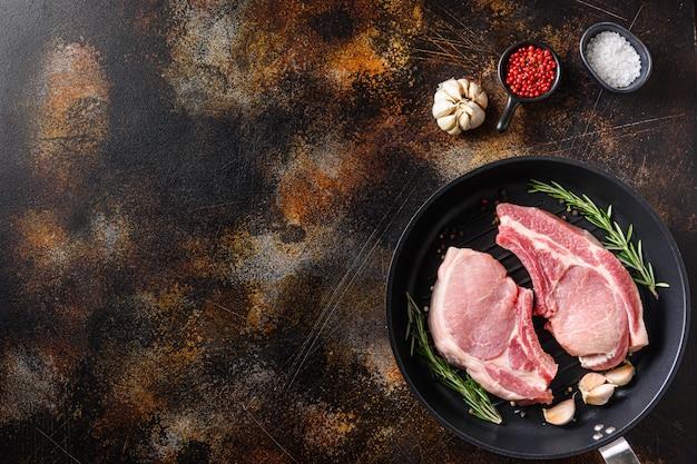 Varkensvlees, kotelet in een zwarte koekenpan grill op een oud rustiek donker metalen oppervlak