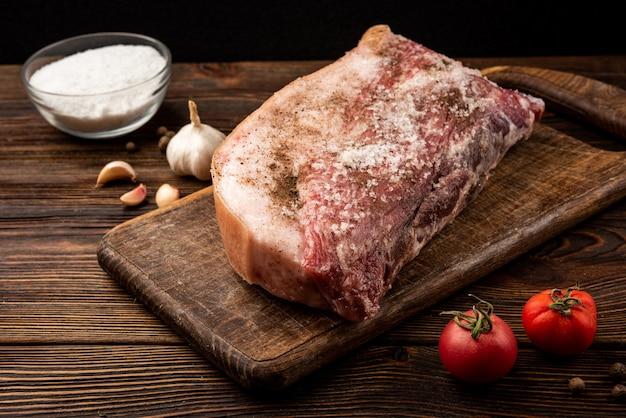 Varkensvlees met kruiden op donker hout.