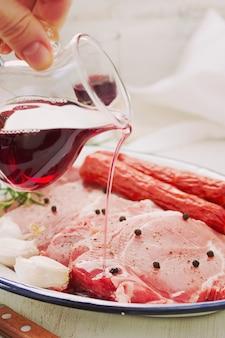 Varkensvlees met zwarte peper, gerookte worstjes en knoflook op schotel met rode wijn