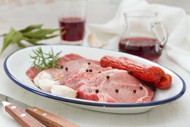 Varkensvlees met zwarte peper, gerookte worstjes en knoflook op schotel