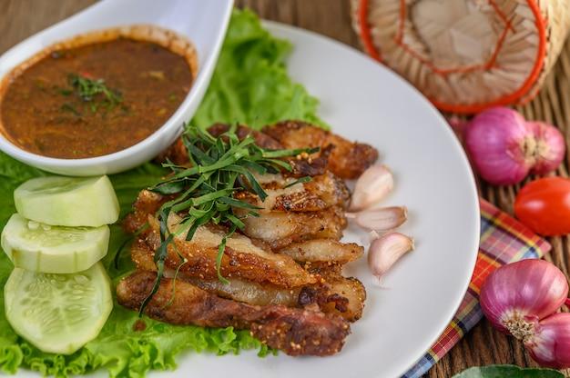 Varkensvlees nek gegrild op een witte plaat met rode ui, tomaat en chili op de houten tafel.