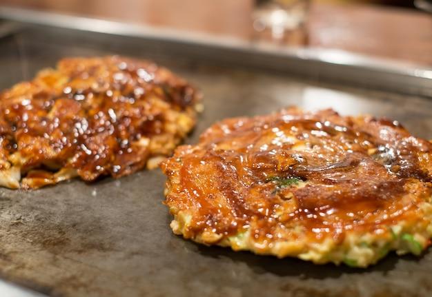 Varkensvlees okonomiyaki op hete pan