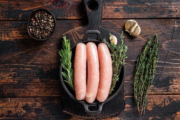 Varkensvlees rauwe worstjes in een pan met kruiden. donkere houten achtergrond. bovenaanzicht.