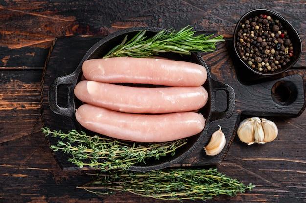 Varkensvlees rauwe worstjes in een pan met kruiden
