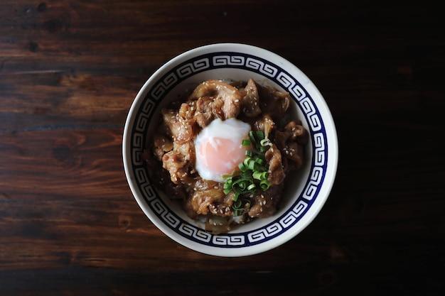 Varkensvlees rijstkom met ei op hout backround japans lokaal voedsel butadon
