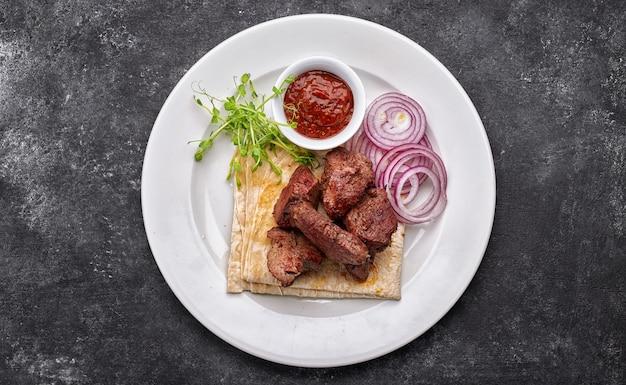 Varkensvlees, rundvlees, lamssjasliek, met saus, uien en lavas, op een wit bord, op een donkere achtergrond
