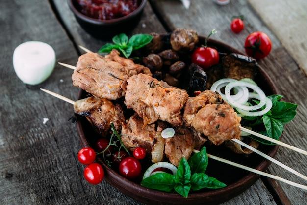 Varkensvlees shish kebab met groenten en tomatensaus close-up op een houten tafel