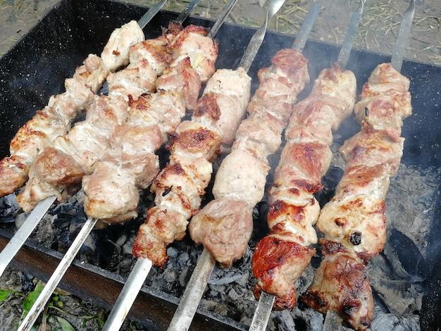 Varkensvlees shish kebab op spiesjes wordt gebakken op kolen in de grill