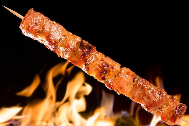 Varkensvlees spies boven vuurvlammen. panceta