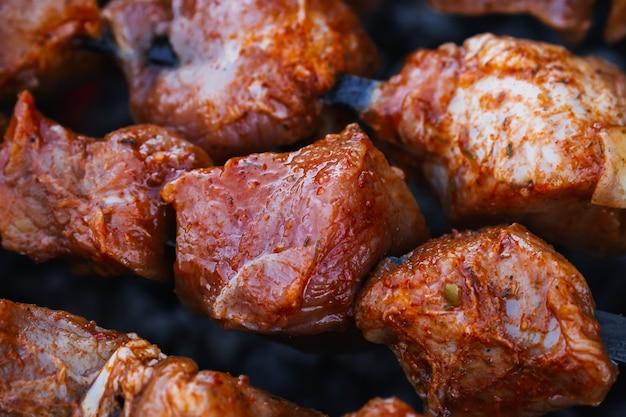Varkensvlees wordt gekookt op spiesjes op de barbecue