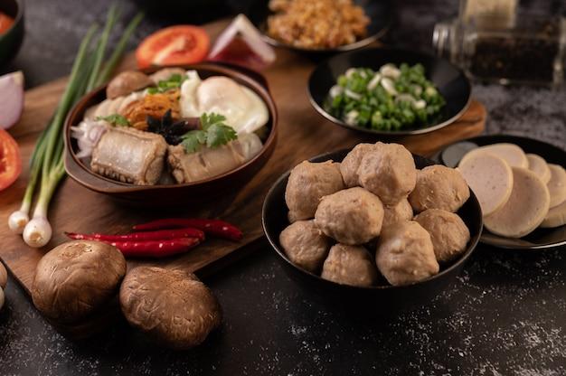 Varkensvleesballetjes in zwarte kopjes met lente-ui, chili, shiitake-paddenstoel en tomaat.