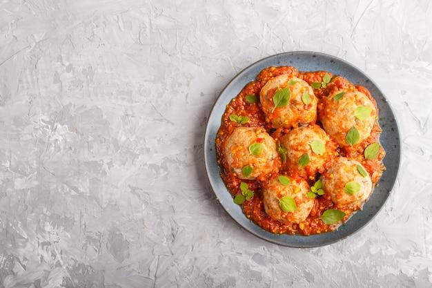 Varkensvleesballetjes met tomatensaus, oregobladeren, specerijen en kruiden op een grijze concrete achtergrond. bovenaanzicht