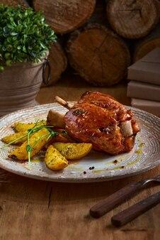 Varkensvleesgewricht met aardappelen in de schil op rustieke keukenlijst bij donkere houten achtergrond, vooraanzicht. varkensbout gedaan, duits eten