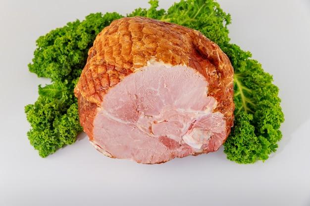 Varkensvleesham gesneden met kruid op wit geïsoleerd