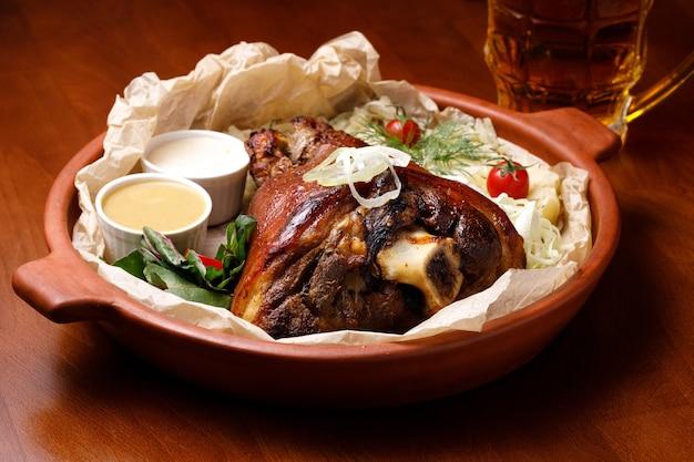 Varkensvleesknokkel met mosterd en witte saus in een kleiplaat en een glas licht bier op een houten tafel. het concept van maaltijden