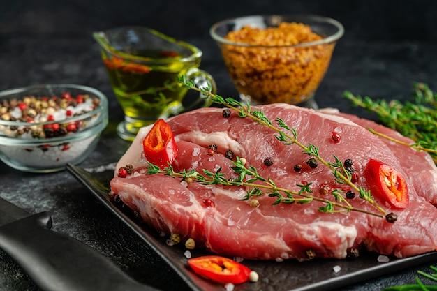 Varkensvleeslapje vlees op zwarte leiplaat met kruiden en specerijen