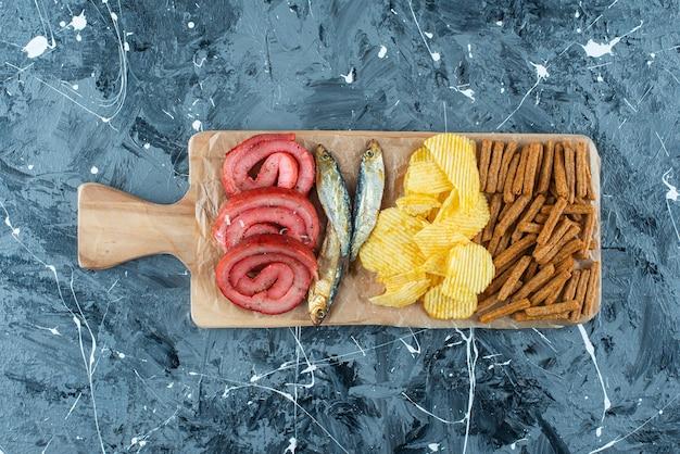 Varkensvleesreuzel, vis, chips en paneermeel op snijplank op blauw.