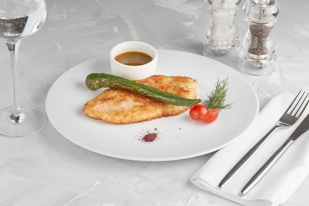 Varkensvleesschnitzel op een witte plaat, lichte achtergrond