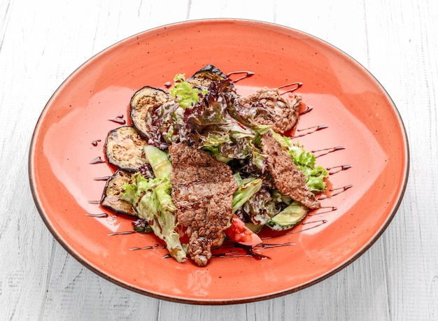 Varkensvleesvlees met verse groentesalade wordt geroosterd op een witte plaat die.