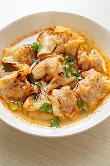 Varkenswontonsoep of varkensknoedelsoep met geroosterde chili - aziatische eetstijl