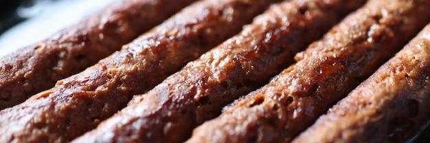 Varkensworsten worden gebakken in pan close-up