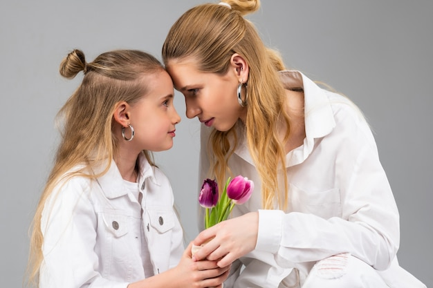 Vastberaden aantrekkelijke vrouw die haar voorhoofd verbindt met haar jongere zus terwijl ze bloemen presenteert
