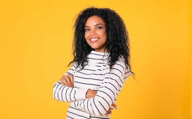 Vastberaden afro-amerikaanse vrouw poseert op een gele achtergrond met haar handen gevouwen, draagt een gestreepte hoodie en kijkt met vreugde naar de camera