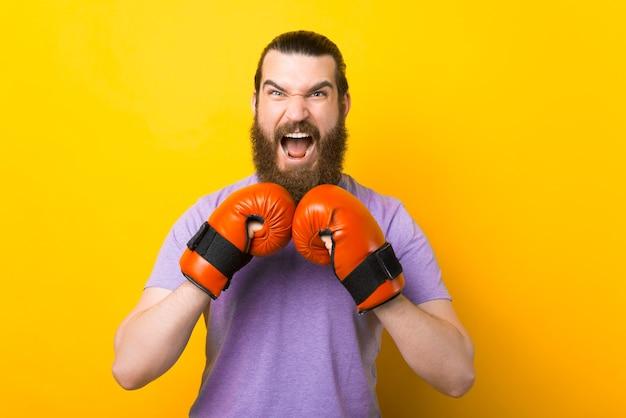 Vastberaden bebaarde man draagt een paar rode bokshandschoenen.