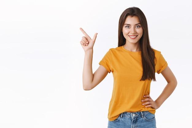 Vastberaden, goed uitziende gemotiveerde vrouwelijke professional weet wat je nodig hebt, wijzend linkerbovenhoek glimlachend assertief en zelfverzekerd, hand op heup, staande witte achtergrond verzekerd
