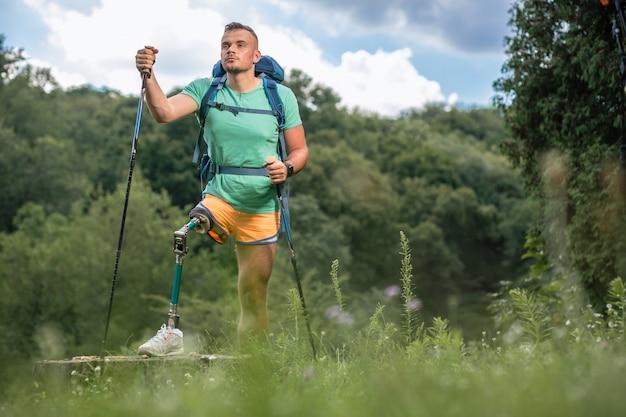 Vastberaden jonge mannelijke toerist met prothese die nordic walking probeert terwijl hij geniet van zijn actieve weekend