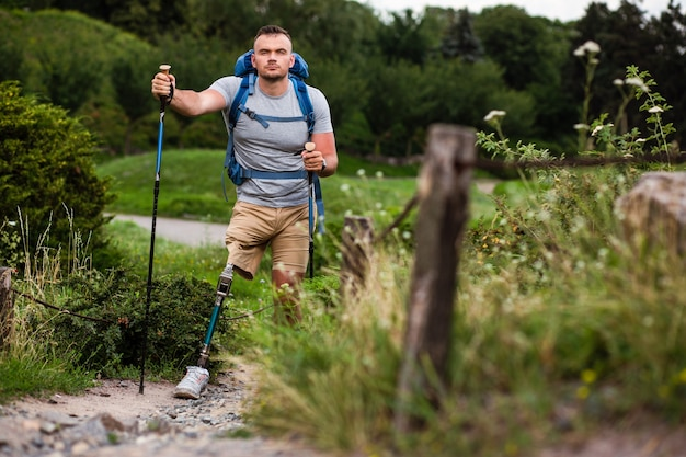 Vastberaden jongeman met prothese die nordic walking probeert terwijl hij actief zijn weekend doorbrengt