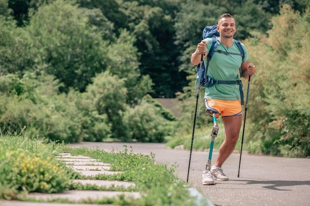 Vastberaden lachende jonge man met verlamming genietend van nordic walking buitenshuis