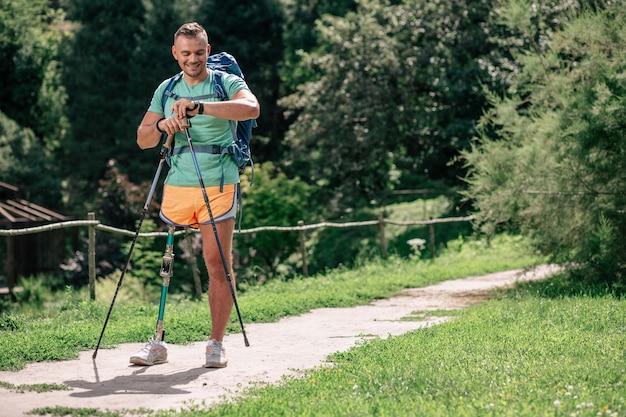 Vastberaden positieve man met verlamming die geniet van nordic walking terwijl hij een gezonde levensstijl leidt