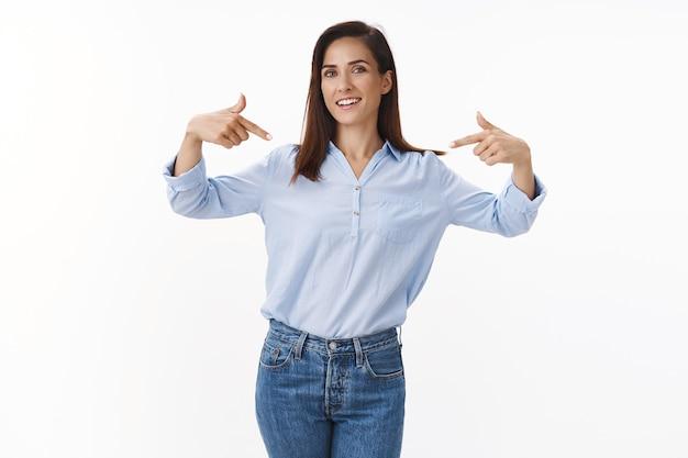 Vastberaden professionele vrouw-ondernemer die opschept over prestatie, trots op zichzelf wijst, persoonlijke overwinningsprestatie praat, gelukkig glimlacht, promotie ontvangt, wordt geplukt, op een witte muur staat