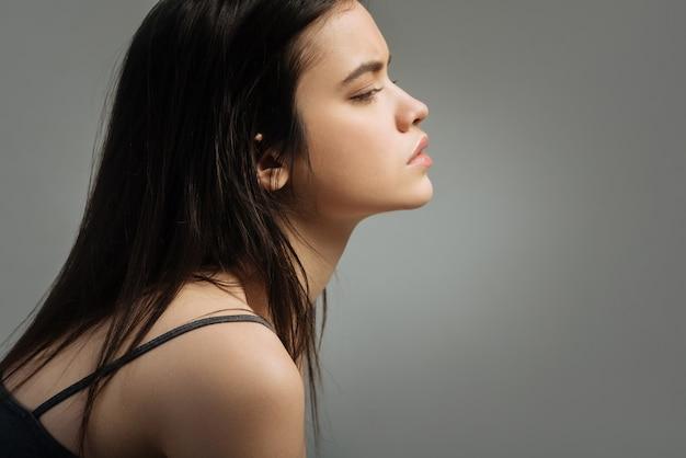 Vastbesloten. vrij steenachtige langharige jonge vrouw die in de verte denkt en kijkt en een top draagt