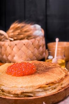 Vastenavond maslenitsa week festivalmaaltijd. stapel russische pannenkoeken met rode kaviaar. rustieke stijl, vrije ruimte voor tekst,