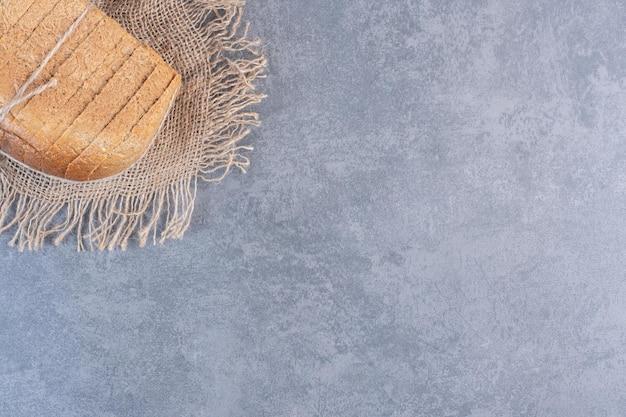 Vastgebonden blok gesneden brood op een stuk doek op marmeren achtergrond. hoge kwaliteit foto