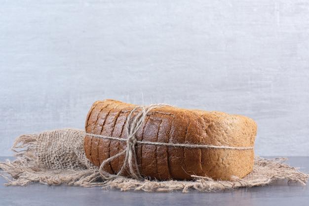 Vastgebonden blok gesneden brood op een stuk stof op marmer.
