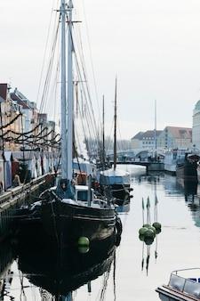 Vastgelegde zeilboten in kanaal van stad