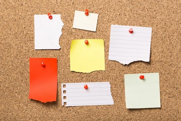 Vastgezette papieren notities op kurk boord