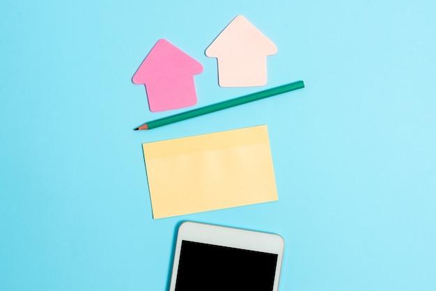 Vastgezette verscheidenheid aan lege kleur papier sticker notes mock up gebruikt voor inhoud. papieren notebookaccessoires en schoolbenodigdheden met mobiele telefoon gerangschikt op verschillende platliggende achtergronden
