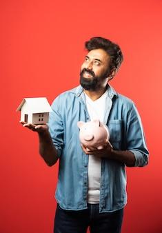 Vastgoed kopen en mensen concept. indiase bebaarde man met miniatuur huismodel, sleutels en spaarvarken op rood