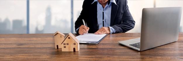 Vastgoed, onroerend goed en huiseigenaar ondertekenen contract door bankagentschap concept, klein houten huis model op kantoor tafel met ondertekening op huurovereenkomst papier te huur boven genoemde woning