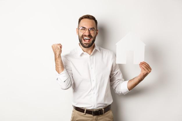 Vastgoed. tevreden man verheugt zich over het oprichten van een perfect huisappartement, met papieren huismodel, staande op een witte achtergrond.