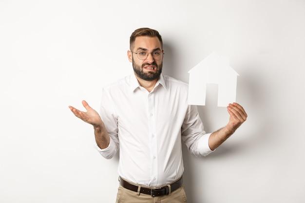 Vastgoed. verwarde man die zijn schouders ophaalt, huis papieren model toont en besluiteloos kijkt, staande op een witte achtergrond. kopieer ruimte